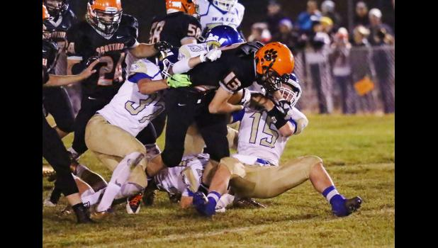 Philip's Nick Donnelly keeps working for every inch toward the goal line, even against four Wall tacklers. (Barb Hockenbary photo)