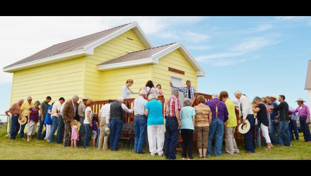 Congregants gather around the Children's Chapel to pray over it during its dedication. Many hands went into refurbishing the structure.