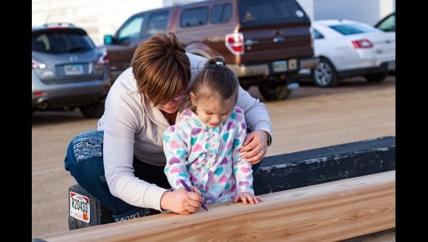 "Ashley Geigle helps daughter Melaynee Geigle sign her name on the Avera beam. Melaynee was diagnosed with low grade neuroblastoma at 10 months old in August of 2014. When Melaynee was 15 months old she had the tumor removed and was declared in remission in November of 2015. Melaynee now has scans every six months and thing are looking great! Ashley Geigle quotes, ""When you hear that your child has cancer, the pain is unexplainable. When Melaynee was declared in remission, we shouted for joy! We would like t"