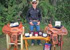 Cash Wilson, a junior at  Wall High School, stands behind his hard work, accomplishments, and earnings from this summer. Pictured are his winnings since the first week of June 2017:two saddles, nine buckles, and a set of spurs.